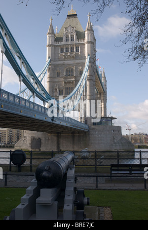 Tower Bridge and cannon from the grounds of the Tower of London, London, England, UK. - Stock Photo