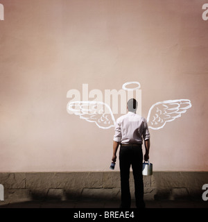 man with angel wings painted on a wall - Stock Photo