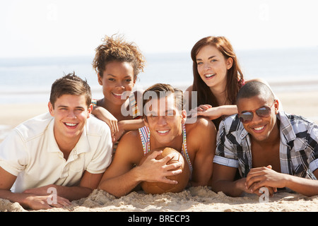 Group Of Friends Relaxing On Beach With Football Together - Stock Photo