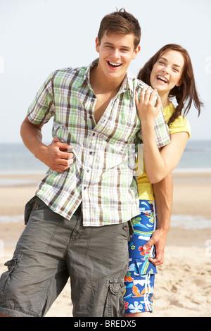 Romantic Teenage Couple Embracing On Beach - Stock Photo