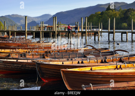 Two girls chatting while seated on the landing stage by the rowing boats on Derwentwater, Keswick - Stock Photo