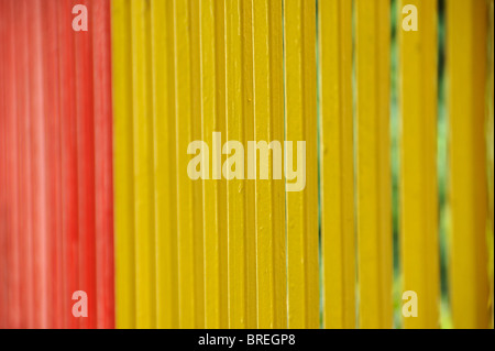 Brightly painted metal fence bars background. Selective focus. - Stock Photo