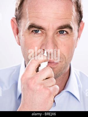 Man using nasal spray - Stock Photo