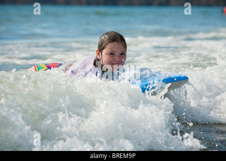 Young girl bodyboarding and enjoying the surf at Newgale beach in Pembrokeshire, Wales, Uk - Stock Photo