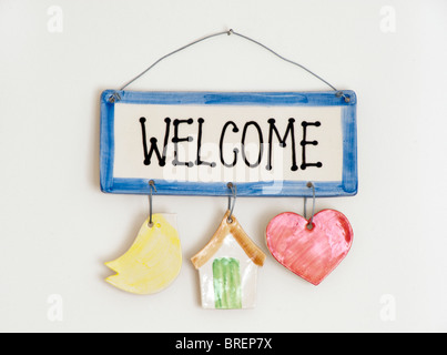 Ceramic welcome plate hanging on a nail and wire on a cream wall - Stock Photo