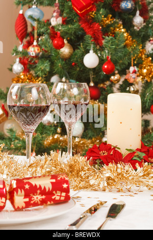 Dining table with christmas crackers, and decorations in front of a christmas tree - Stock Photo