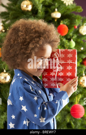 Young Boy Holding Gift In Front Of Christmas Tree - Stock Photo