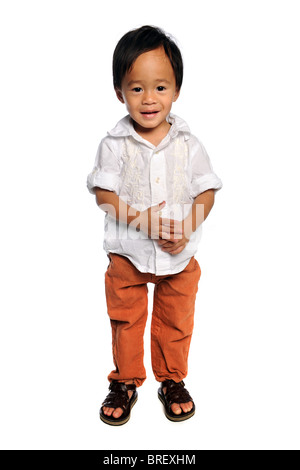 Portrait of young Asian boy standing over white background - Stock Photo