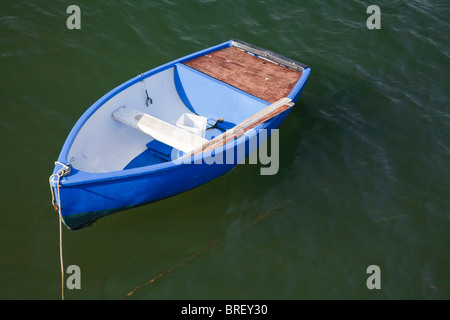 Empty rowing boat painted a bright blue - Stock Photo