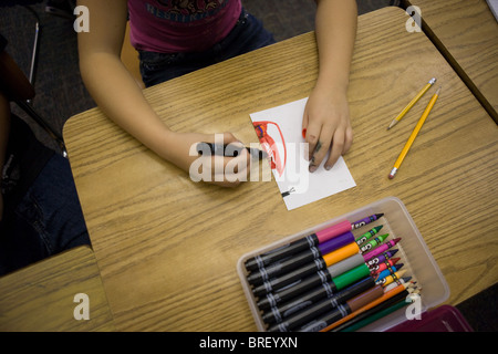 child drawing a pictures with magic markers at a desk - Stock Photo