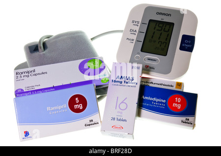 Boxes of various blood pressure medications beside a blood pressure monitor with a very high reading of 190/111 - Stock Photo