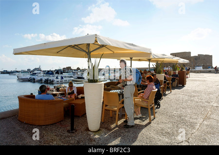 People in a cafe with sun umbrellas at the shore promenade, citadel, Paphos, Pafos, Cyprus, Europe - Stock Photo