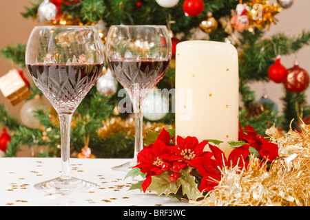 Christmas dining scene with tree, crystal wine glasses and christmas table decorations - Stock Photo