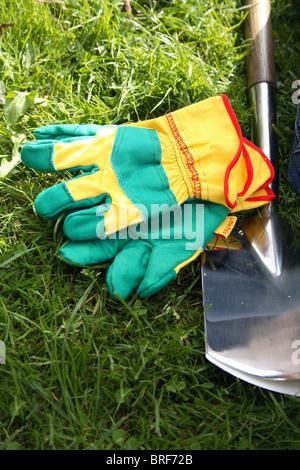 Garden gloves next to spade on a lawn - Stock Photo