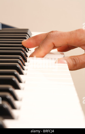 One hand playing on a piano keyboard - Stock Photo