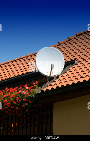 satellite dish on the roof of a new house - Stock Photo