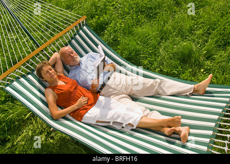 Senior couple lying in a hammock, woman listening to music, man reading a book - Stock Photo