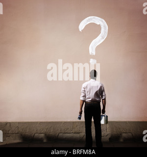 man with question mark painted on a wall - Stock Photo