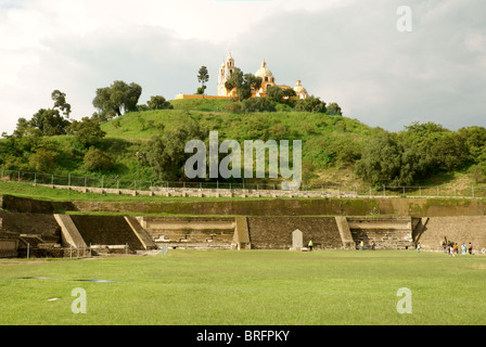 Pre-Hispanic ruins at southern base of Tepanapa Pyramid and Santuario de Nuestra Senora de los Remedios church, - Stock Photo