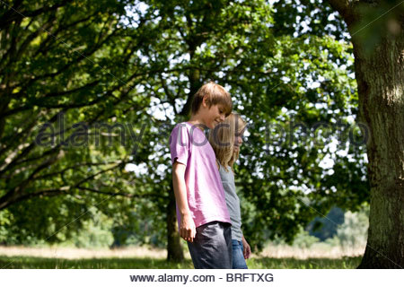 A young boy and girl walking in the park - Stock Photo