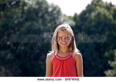 Portrait of a young girl smiling, outdoors - Stock Photo