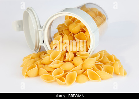 Pile of uncooked Conchiglie pasta shells spilling out of a plastic food container with lid open - Stock Photo