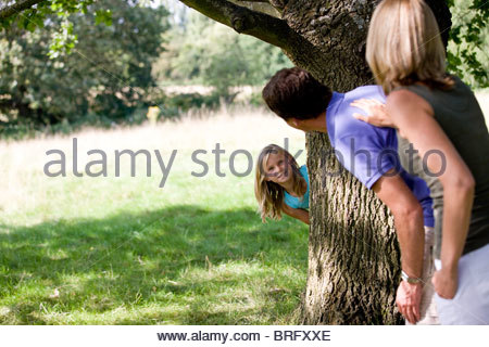 Parents and daughter playing hide and seek - Stock Photo