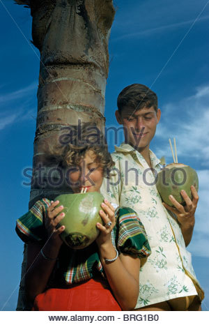 Man holding coconut watches as woman drinks with straw from coconut. - Stock Photo