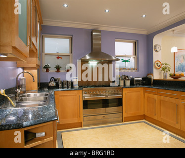 Mauve fitted units in modern kitchen with orange wall for Mauve kitchen walls