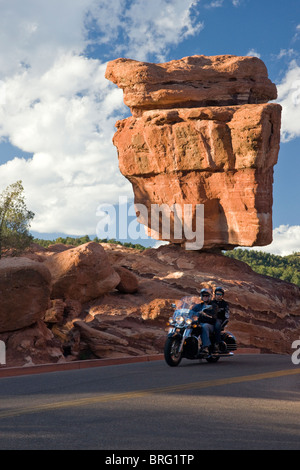 Couple on a motorcycle ride past Balanced Rock, Garden of the Gods, National Natural Landmark, Colorado Springs, - Stock Photo