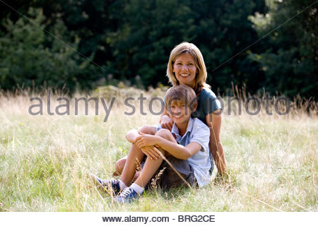 A mother and son sitting on the grass - Stock Photo
