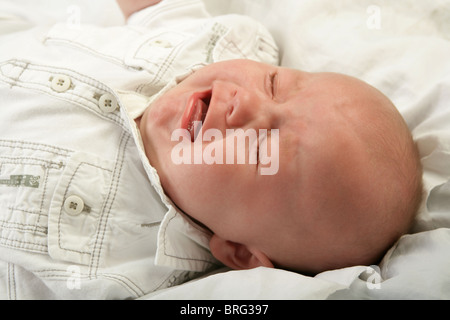 Three month old baby boy crying with his eyes closed. - Stock Photo