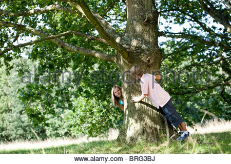 A young boy and girl playing hide and seek - Stock Photo