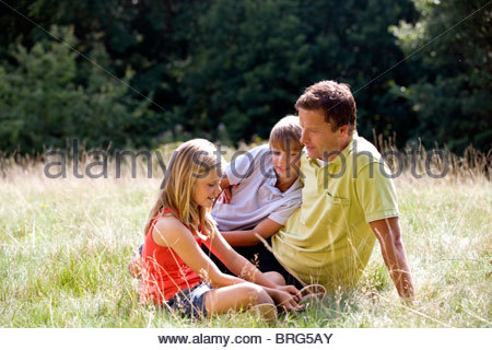 A father and his children sitting on the grass - Stock Photo
