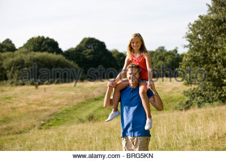 A father carrying his daughter on his shoulders - Stock Photo
