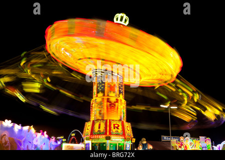Chain carousel with motion blur at night at the Oktoberfest, Munich - Stock Photo