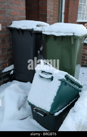 Black and green wheelie bins outside a brick terraced house covered in snow waiting to be collected and emptied - Stock Photo