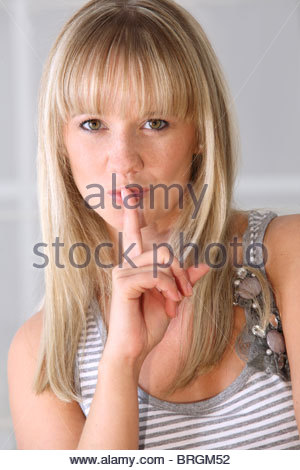 Young woman holding index finger to her lips gesturing silence - Stock Photo