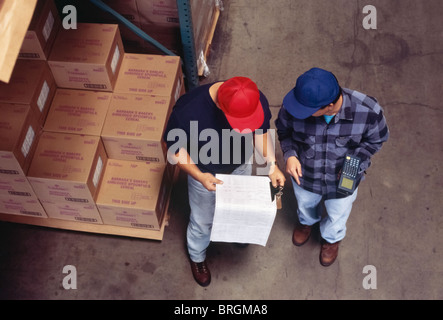 Two Workers Checking Inventory Sheets in Warehouse - Stock Photo