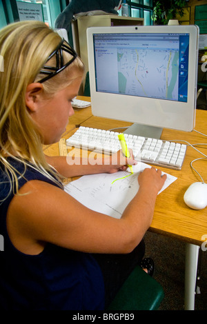 A school girl draws major neighborhood routes on a map downloaded from a computer in San Clemente, CA. - Stock Photo