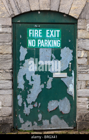 Fire Exit and No Parking signs on a door with peeling paint, Plymouth Barbican area, Devon, UK - Stock Photo