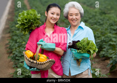 Mother and daughter gardening in farm - Stock Photo