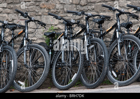 A row of  bicycles for sale parked against a stone wall in Bradford-on-Avon, Wiltshire, UK September 2010 - Stock Photo