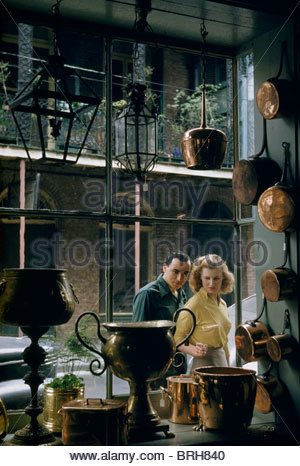 Couple looks at shop window displaying metal arts and crafts objects. - Stock Photo