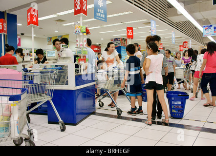 Songjiang, Shanghai, China. Chinese shoppers queuing at checkout pay tills of Tesco supermarket - Stock Photo