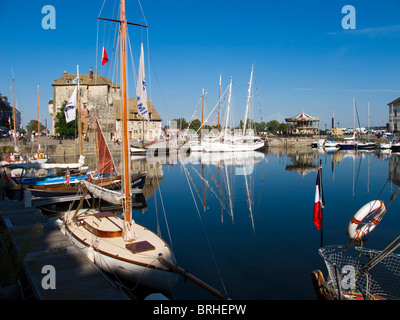 The old port in Honfleur, France showing moored yachts, a merry go round and the Lieutenance building at the Harbour - Stock Photo