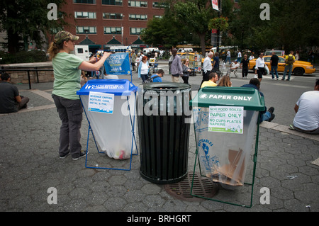 A woman adjusts a recycle here sign for a plastic bottles and aluminium cans bin in Union Square Park in New York - Stock Photo