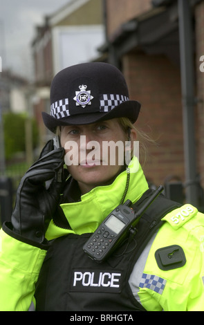Female police officer on a mobile telephone UK - Stock Photo