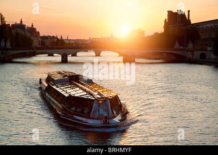 Europe, France, Paris, Tourist Boat on Seine River at Sunset - Stock Photo