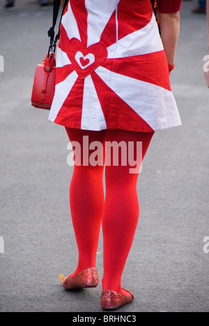 Woman wearing skirt and tights with english colours, heart shapes, UK - Stock Photo